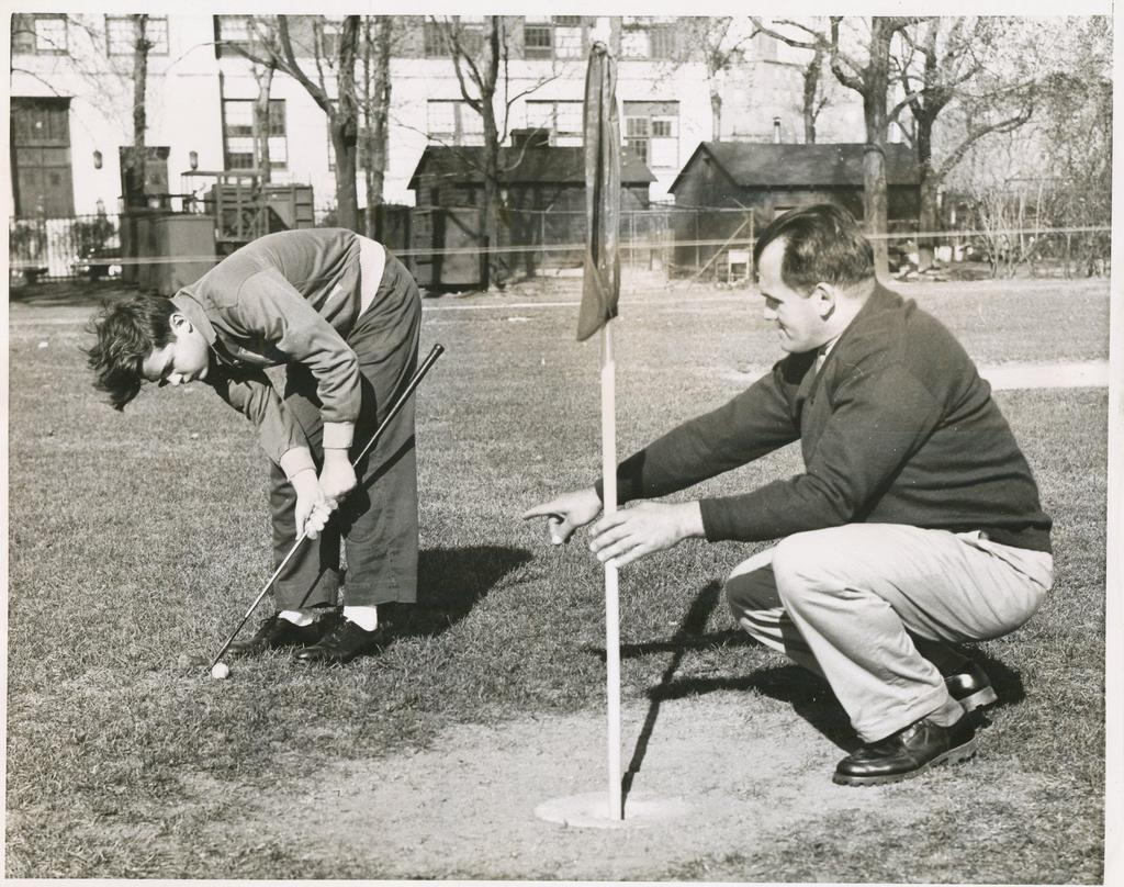 Teacher assisting a student with his golf putting