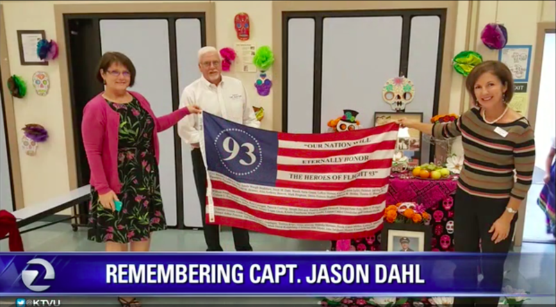 Principal Herbstreith holds a memorial American flag with Jason Dahl's sister and brother-in-law.