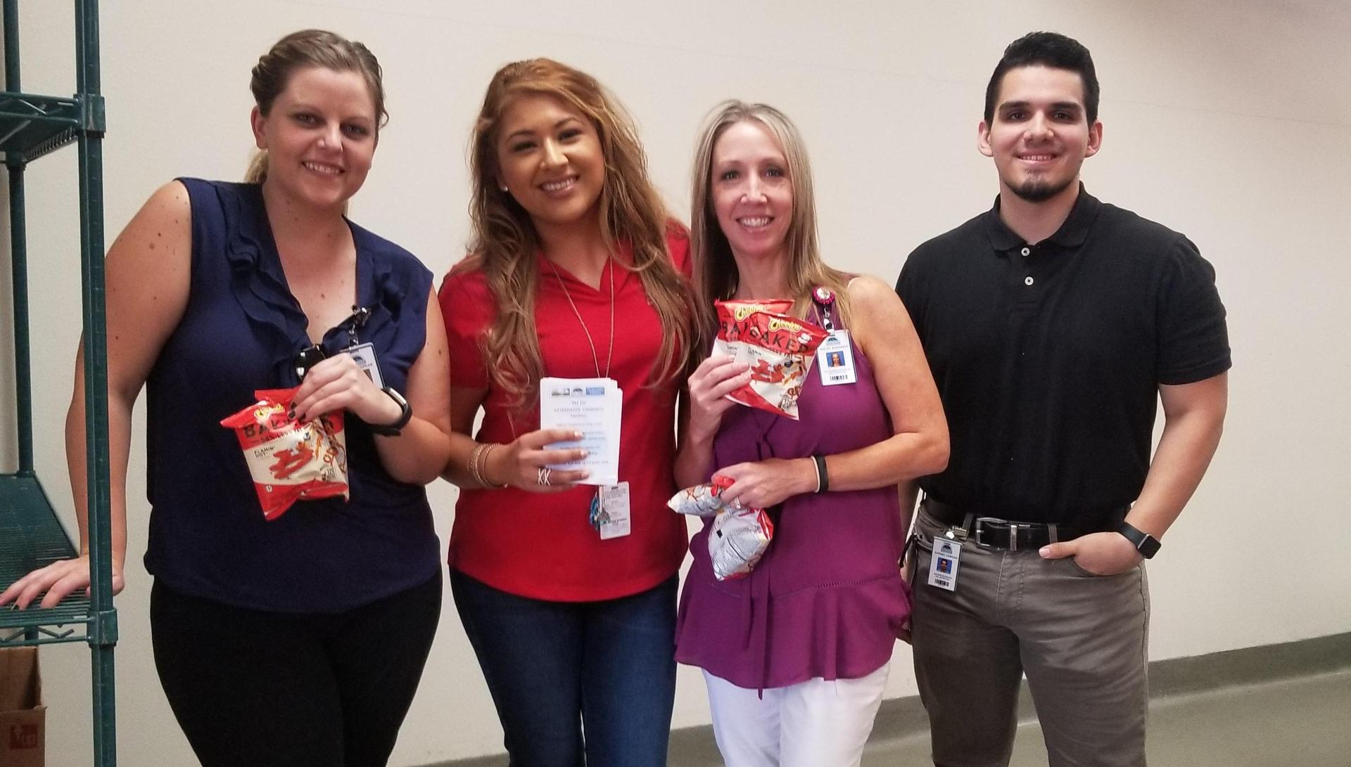Ashley Oostdam, Acct Tech, Cinthia Chavez-Torres, Enrollment Tech, Shelly Ruzzamenti, Account Tech, and Alfonso Cardona, Account Tech. Volunteered for the 'I'm In' attendance campaign. Pictured distributing Hot Cheetos at SJHS.