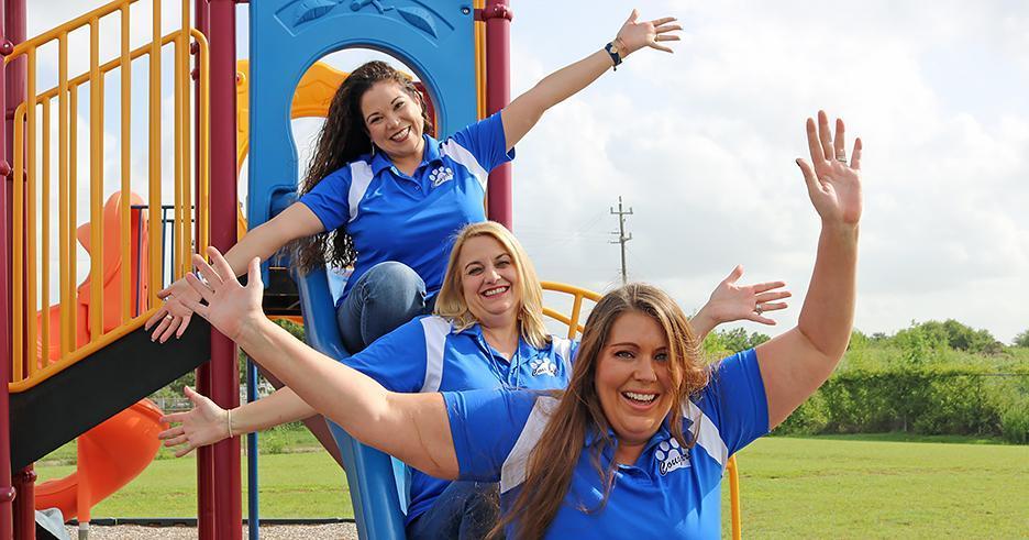 Three woman sliding down a slide