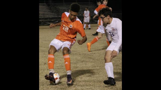 Alex Auzenne kicking the soccer ball.