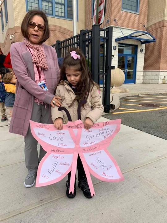 little girl holding a pink and white butterfly with names of classmate