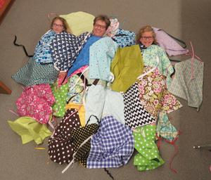 Art teacher Kathy Bailey and two students are completely covered in the handmade aprons.