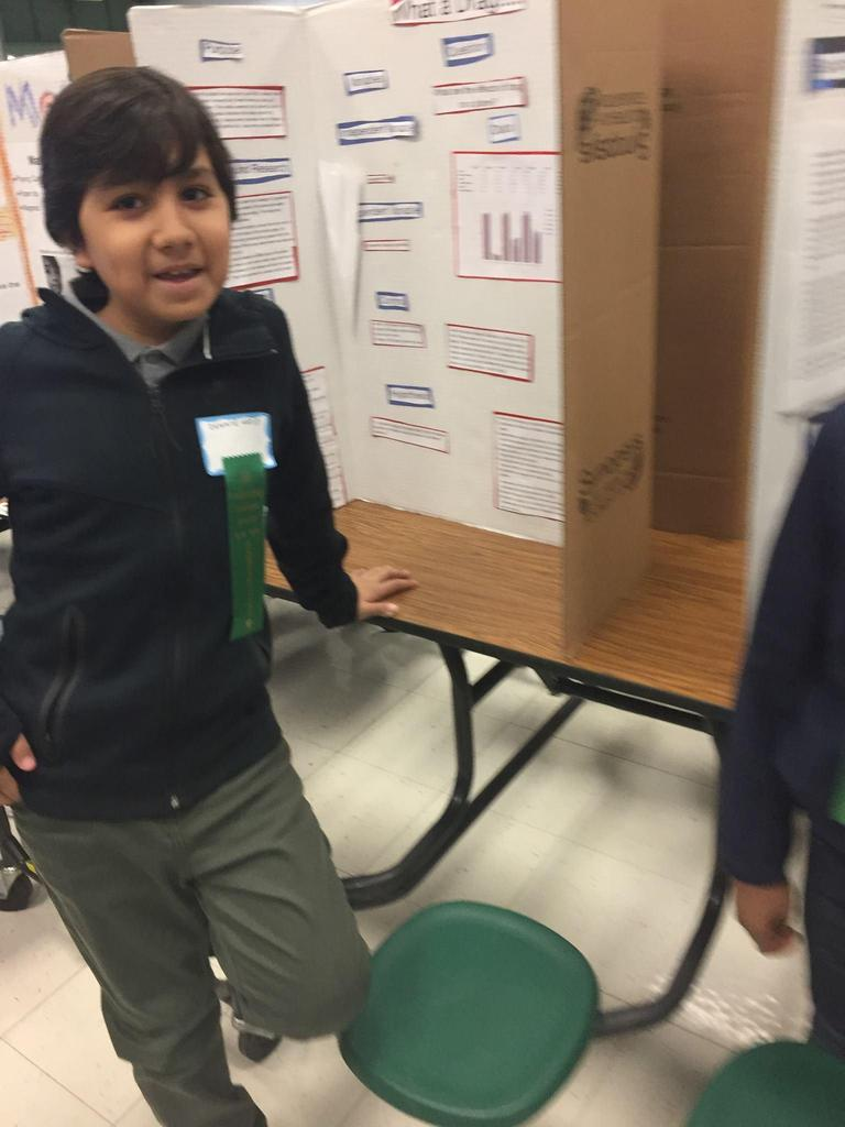 student stands in front of his winning science fair project