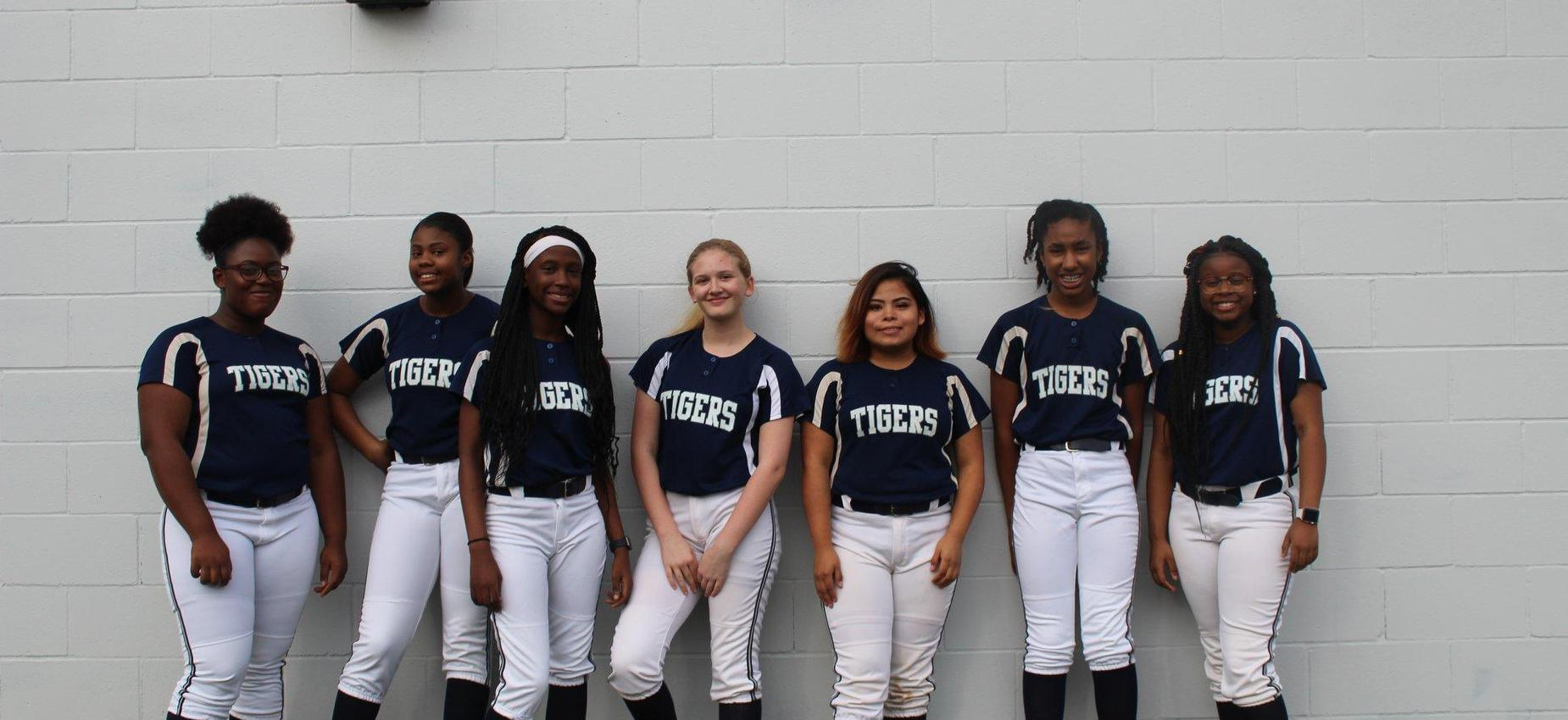girls baseball team lined up against a wall