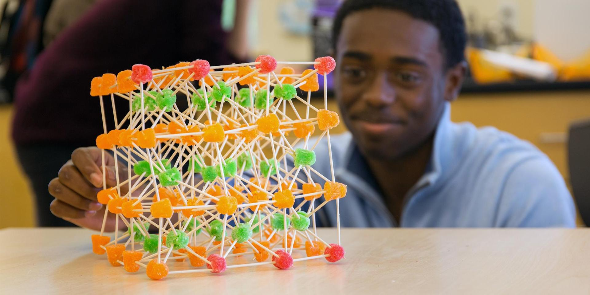 A student admires a 3D model of a tesseract-like cube made out of gumdrops and toothpicks.