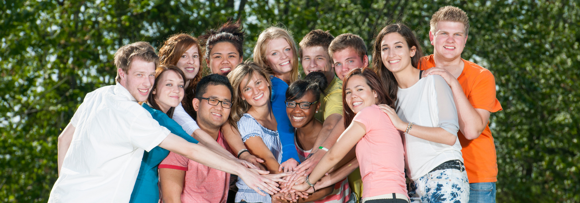 large group of teens stacking their hands together