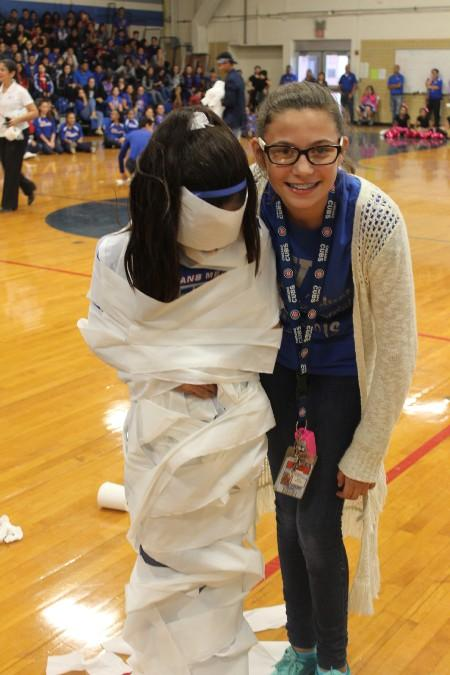 Two sixth graders pose for a photo after completing a toilet paper wrapping game at the Fall pep rally.