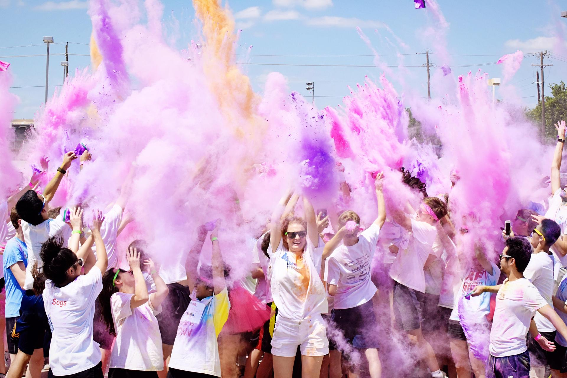 Upper private school students celebrating during color run