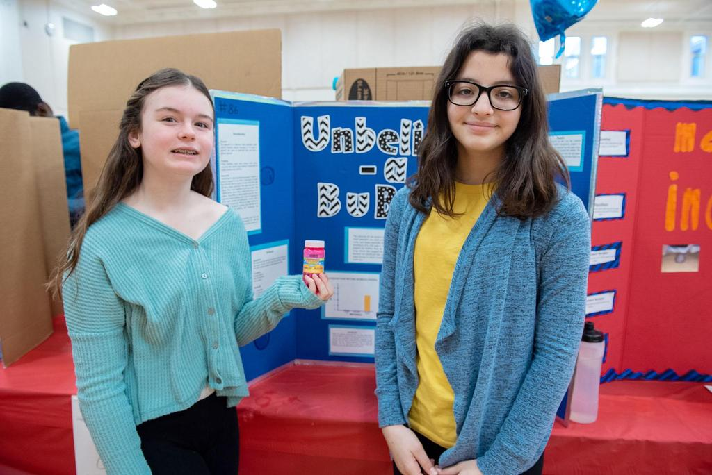 Two middle school students stand in front of their project