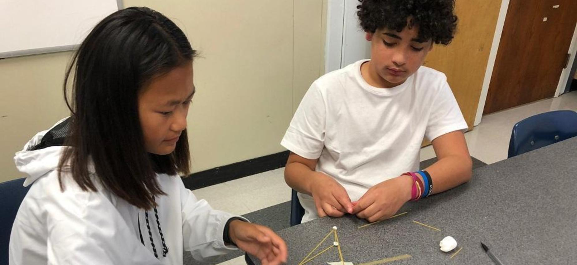 Two students work on a project at a table.
