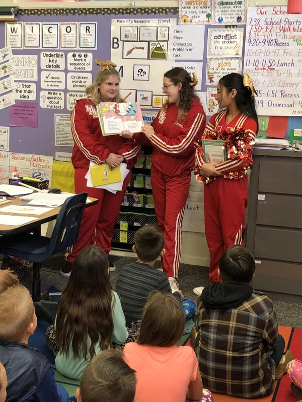 Hemet High School Cheerleaders reading to Little Lake Elemenary School students.