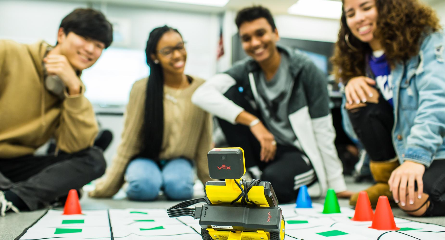 students in computer science class with robot