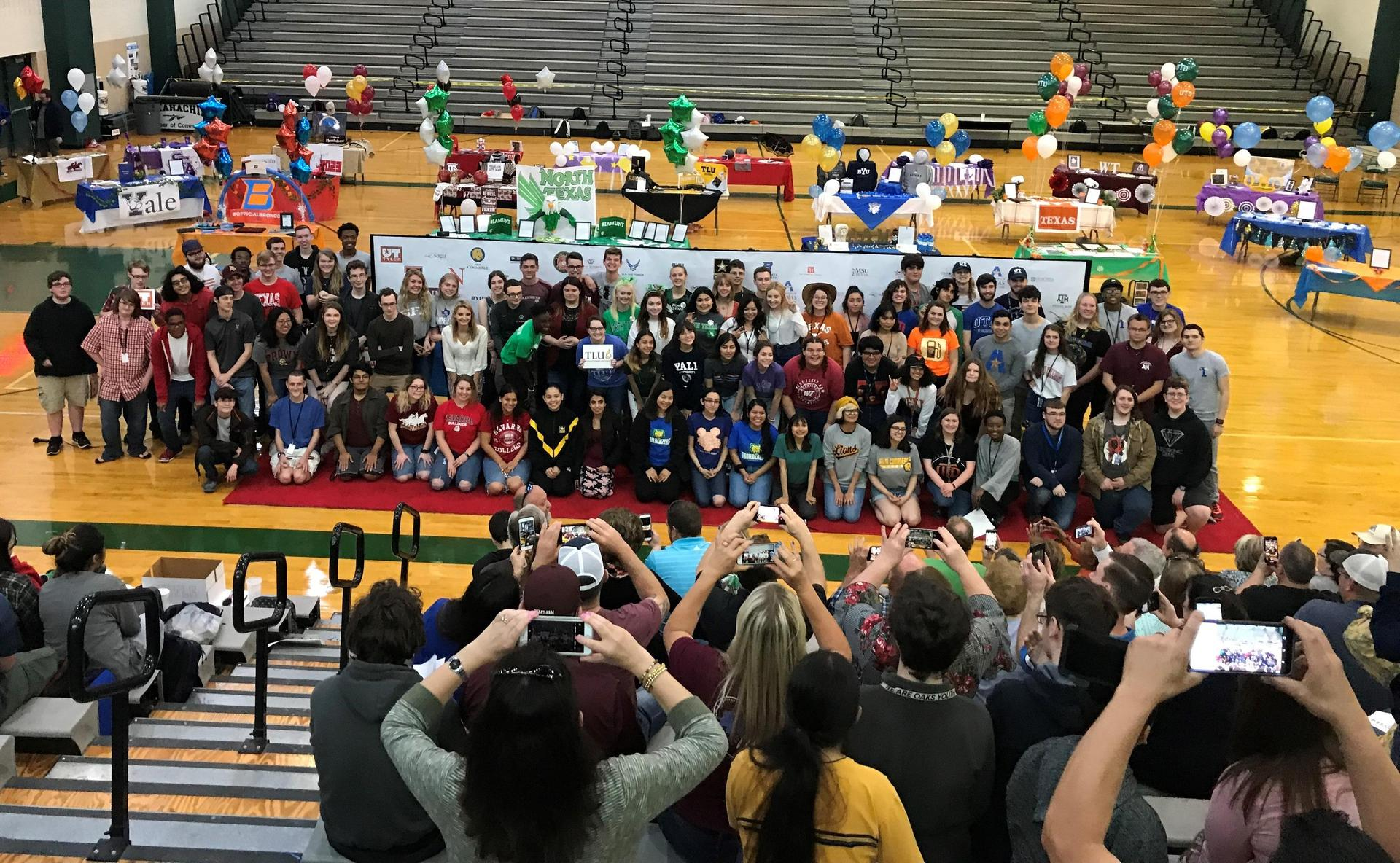 large group of seniors pose together in the shirts of the universities they plan will attend