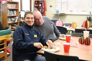 A student and teacher smile during lunch