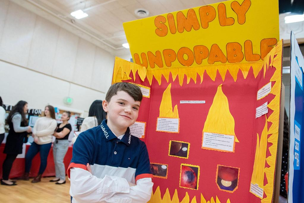 A student stands in front of his project called Simply Unstoppable