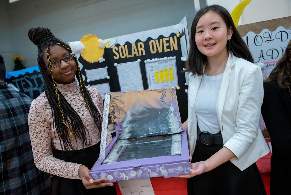 Two students hold their project, the solar oven