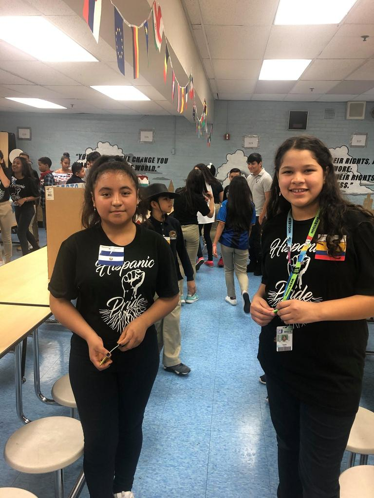 two girls wearing Hispanic Heritage shirts and wearing a small flag of their nation