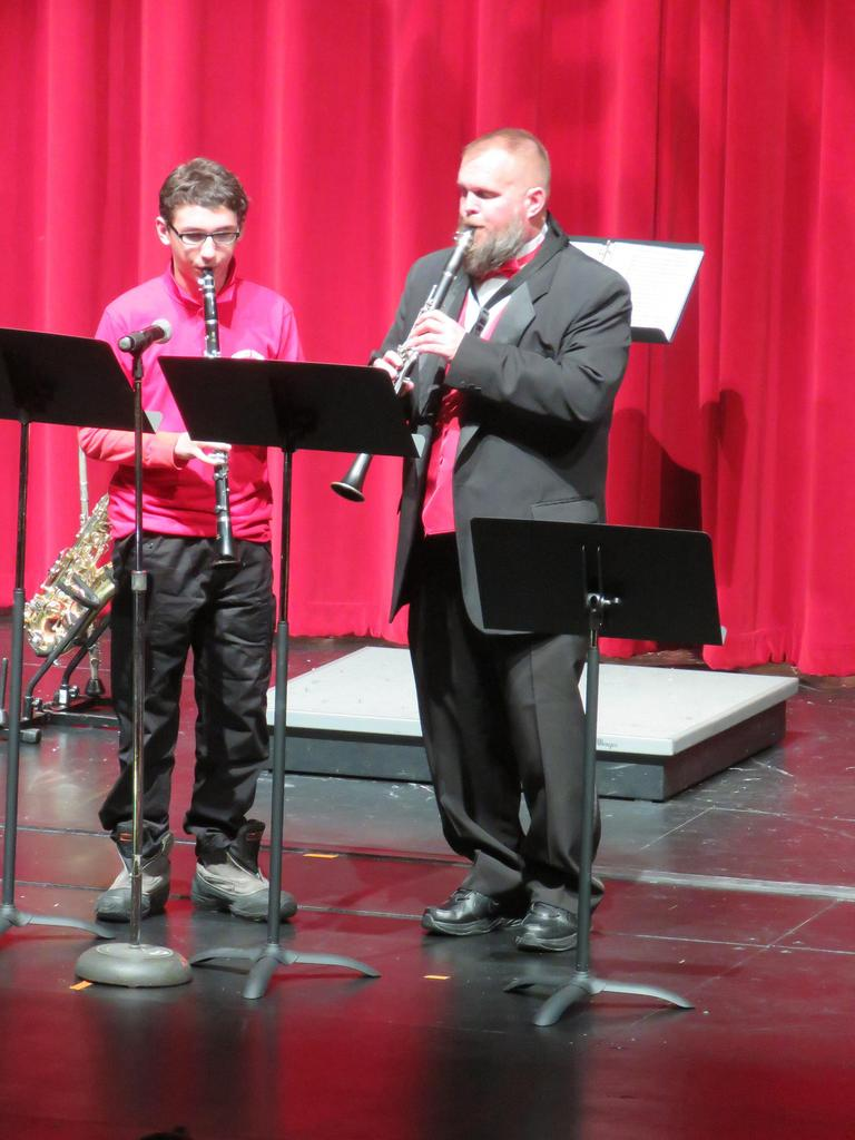 A male student and a teacher play the clarinet at center stage