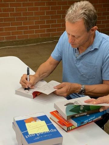 Author Stuart Gibbs signing books