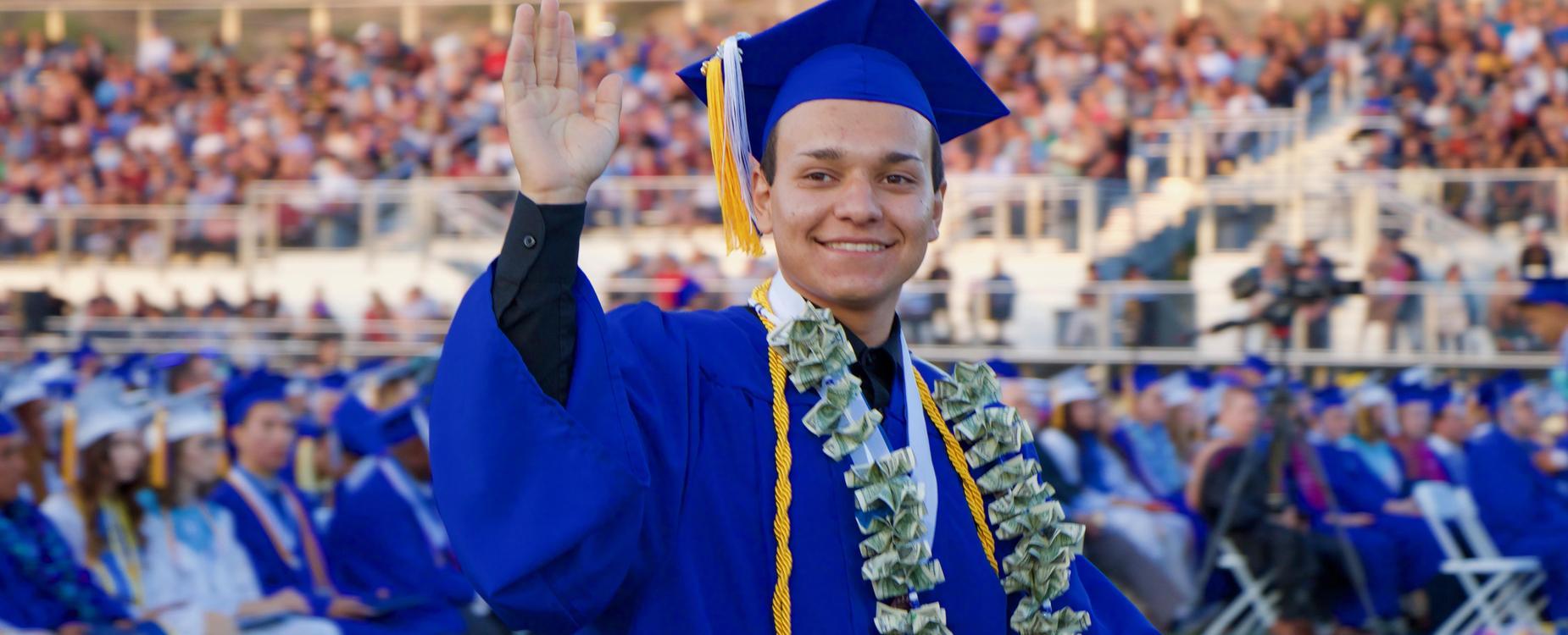 Graduate waving to crowd