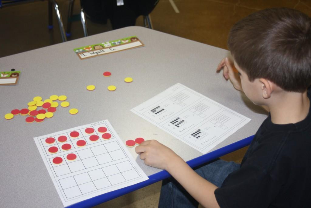 First graders work together to solve math concepts through games.