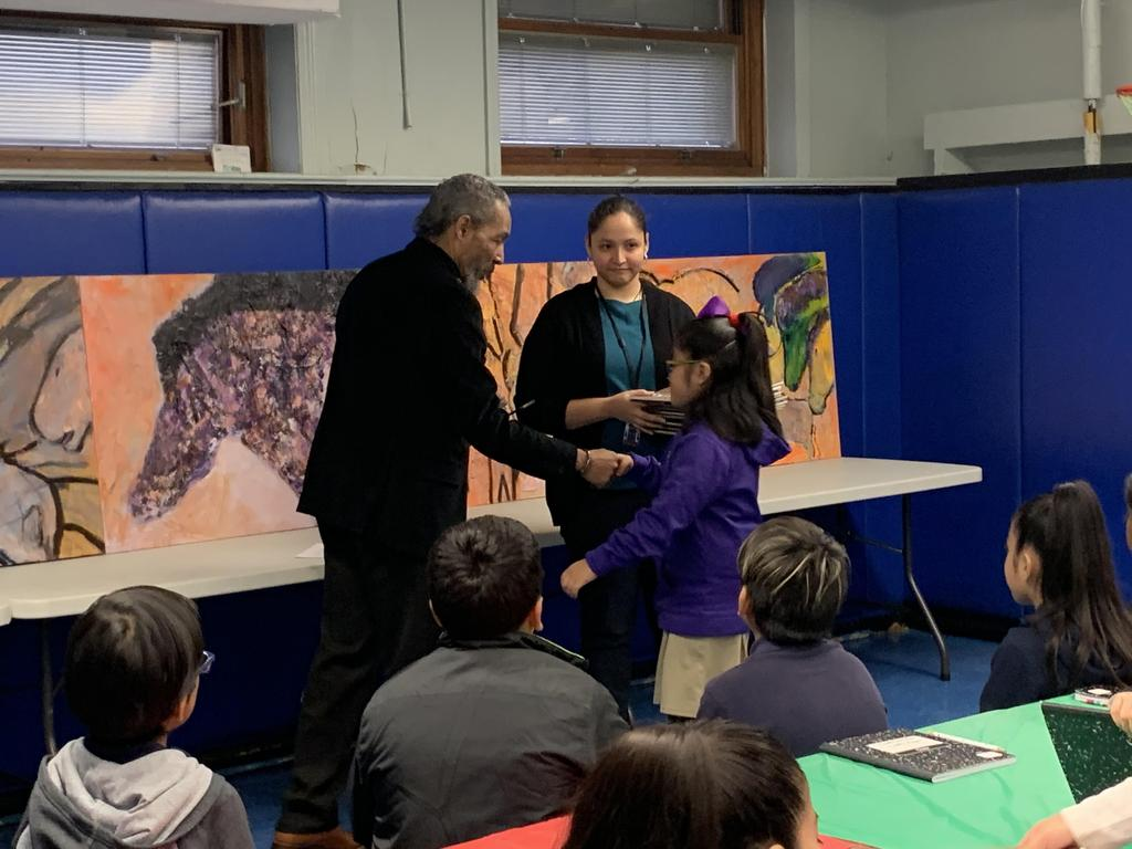 Artist brooks shakes the hand of a girl with glasses as the art teacher holds certificates in her hands