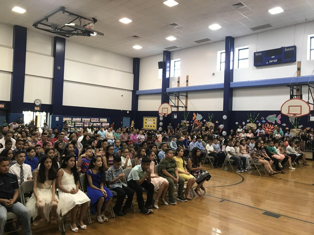 view of parents, friends, and staff seated in the gym