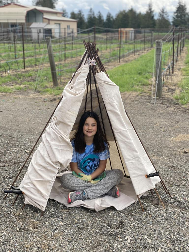 girl sitting in teepee she built