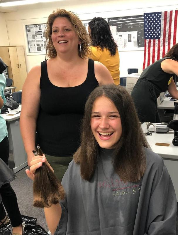 Photo of a Westfield hair stylist cutting teenagers hair to donate to make wigs for children and teens with cancer and other disorders.