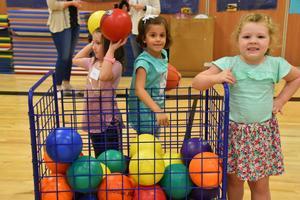 Kindergarten students grabbing bounce balls to play toss.