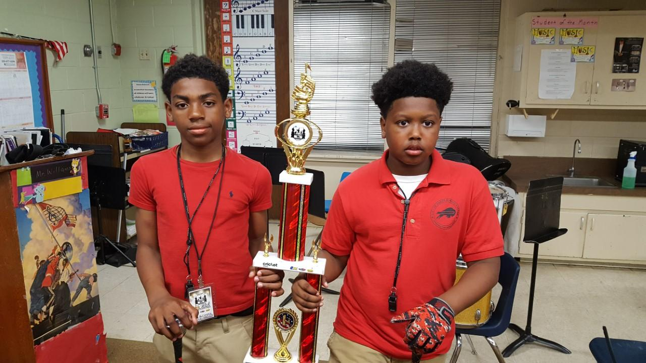 Two Baker Middle Band Students hold winning trophy from battle of the bands