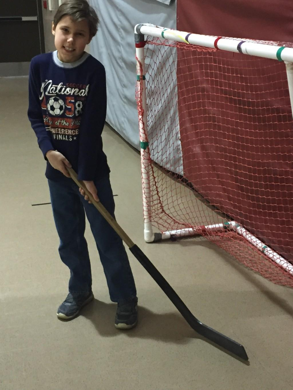 student with hockey stick in gym class