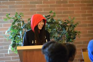 teen girl standing inside brick-walled room and smiling from under red hoodie