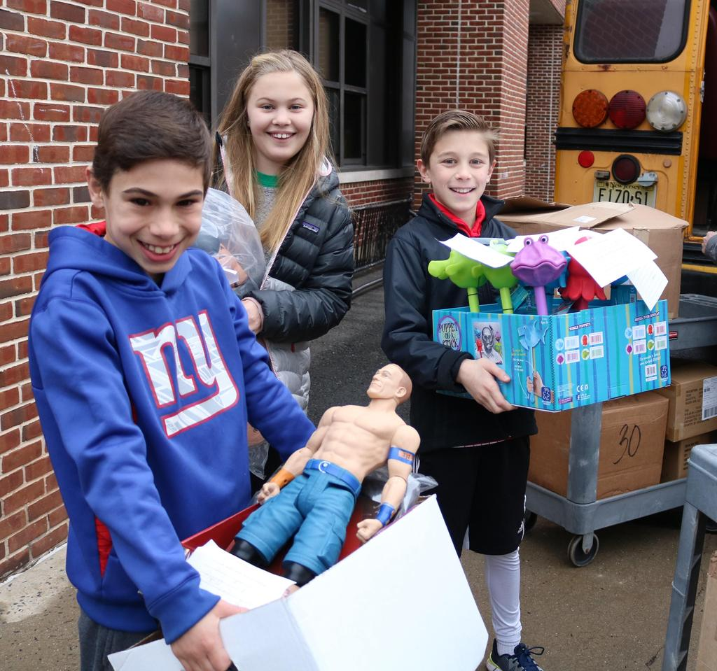 Photo of three Franklin students holding boxes of toys for loading on bus.