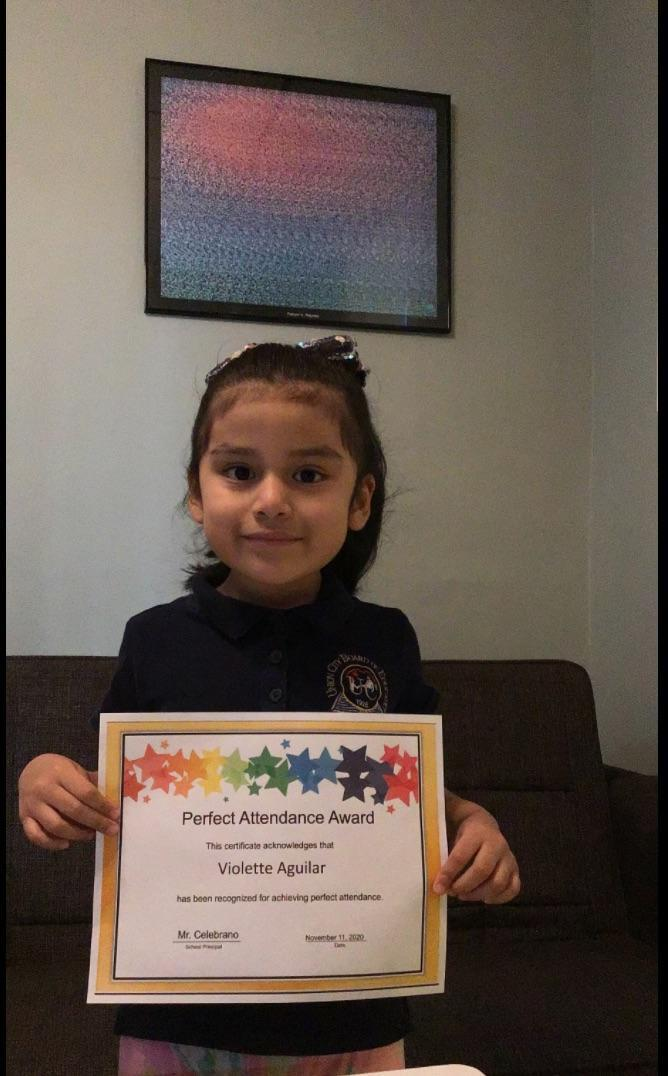 Violette Aguilar holding perfect attendance certificate