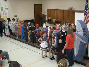 Second and third grade students line up on stage for costume contest.