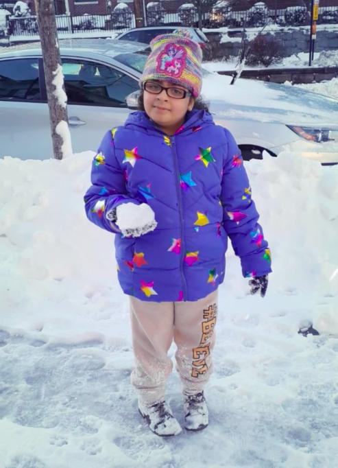 Girl holding snowball outside