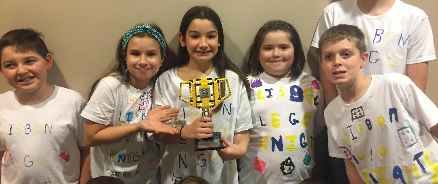 five elementary students stand together holding trophy