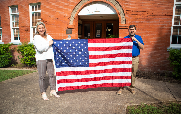 man and woman holding flag