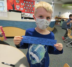 A Lee student write his message of hope on a paper chain link.