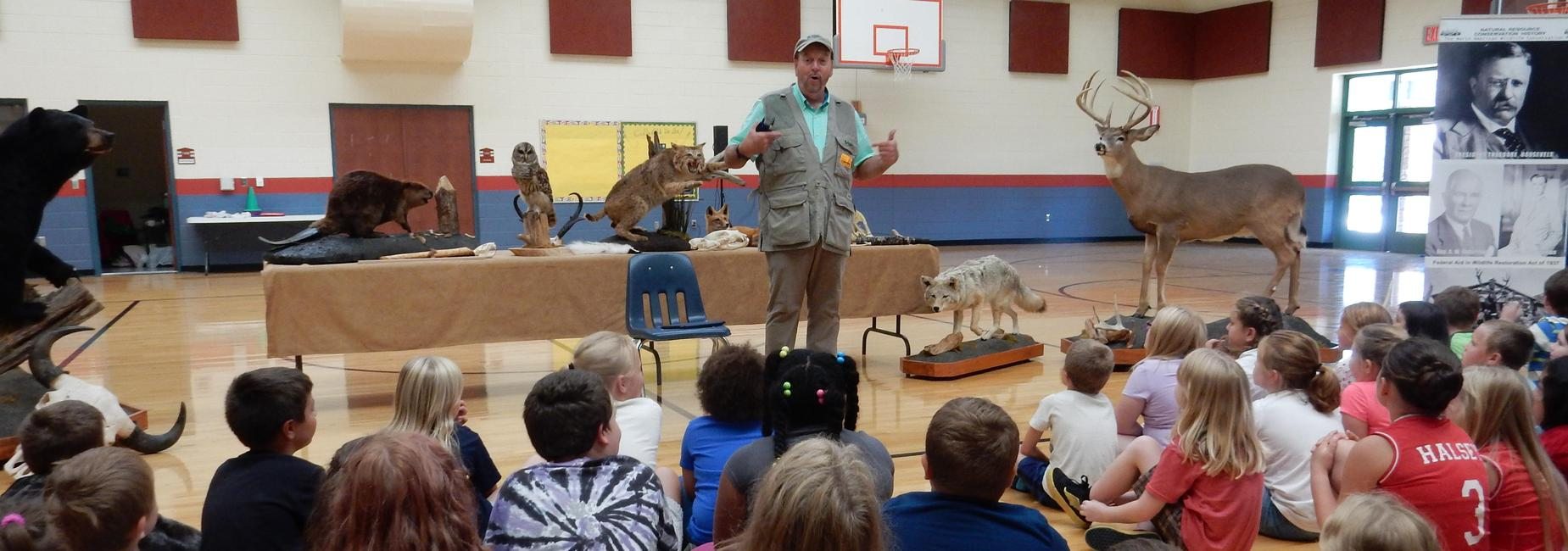 A representative from the Ward Burton Wildlife Foundation, shown with various mounted animals, talks to student assembly