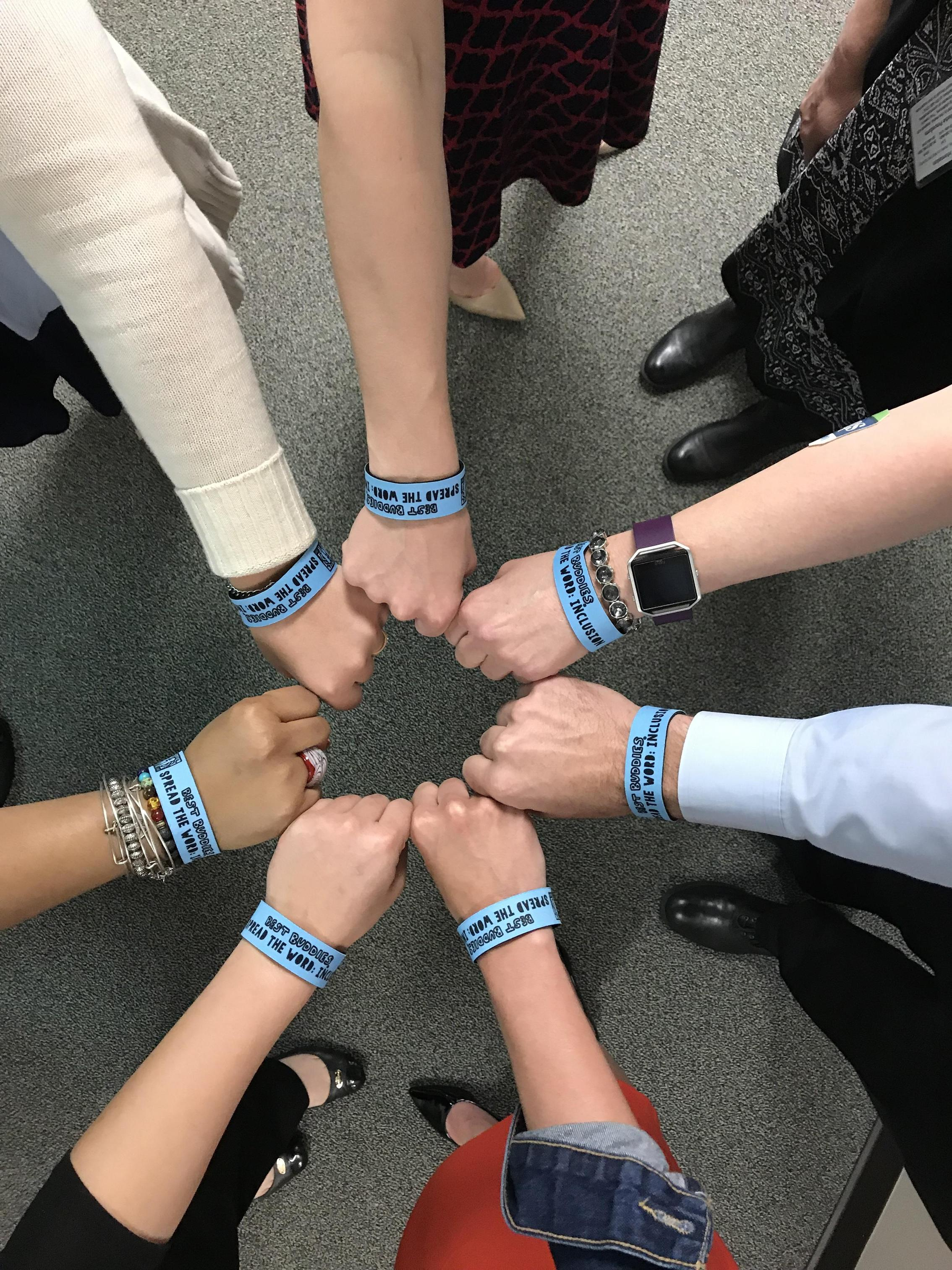 7 fists held together in a circle all wearing wristbands pledging inclusion