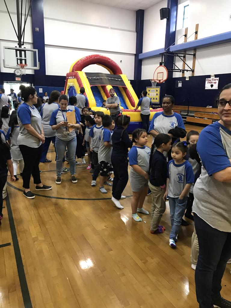 view of children lined up to enter several bouncy houses in the gym