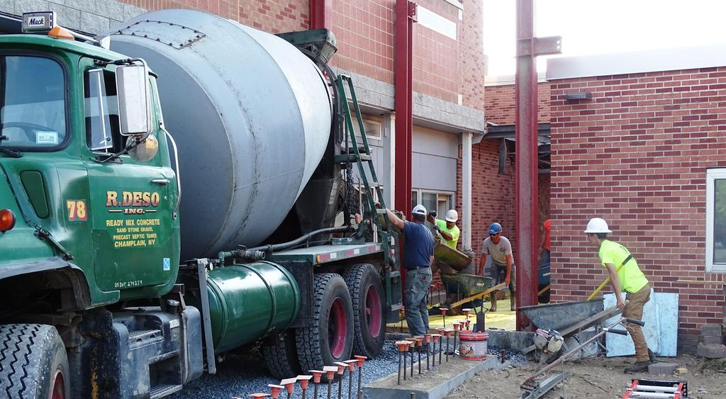 This photograph shows delivery of cement by cement mixer truck to the location of what will soon be the expanded and updated main pedestrian entrance at Beekmantown Elementary School.