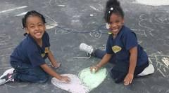 Two DEAW students drawing in the parking lot with chalk