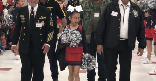 veterans walking with cheerleader