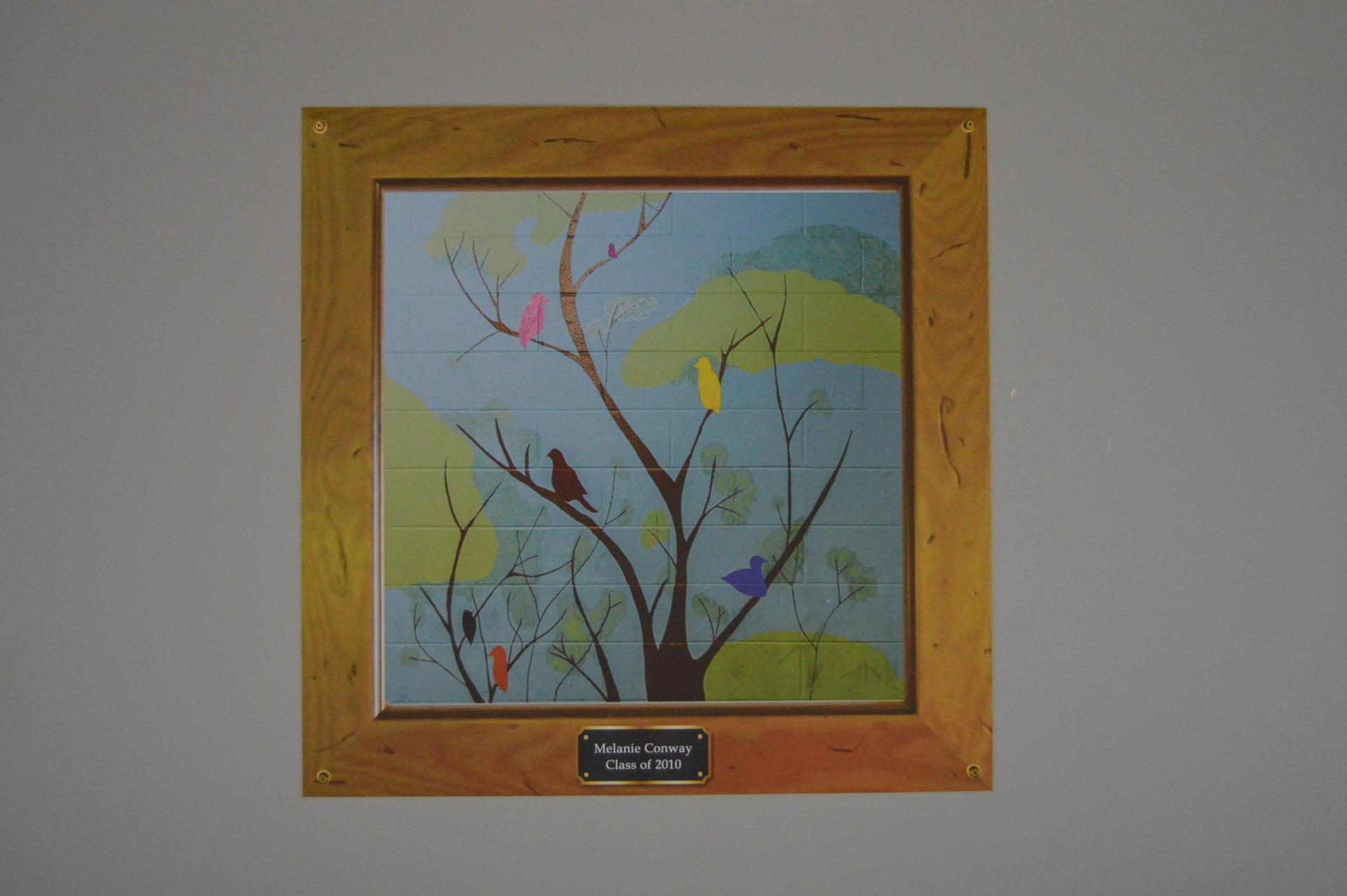 Mural of a brown thin tree with a blue, pink, yellow, orange, purple bird sitting on the branches.