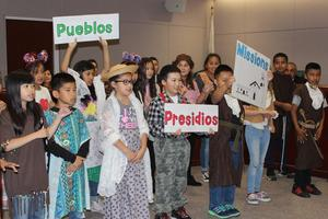 Students hold signs and sign a song about California history.