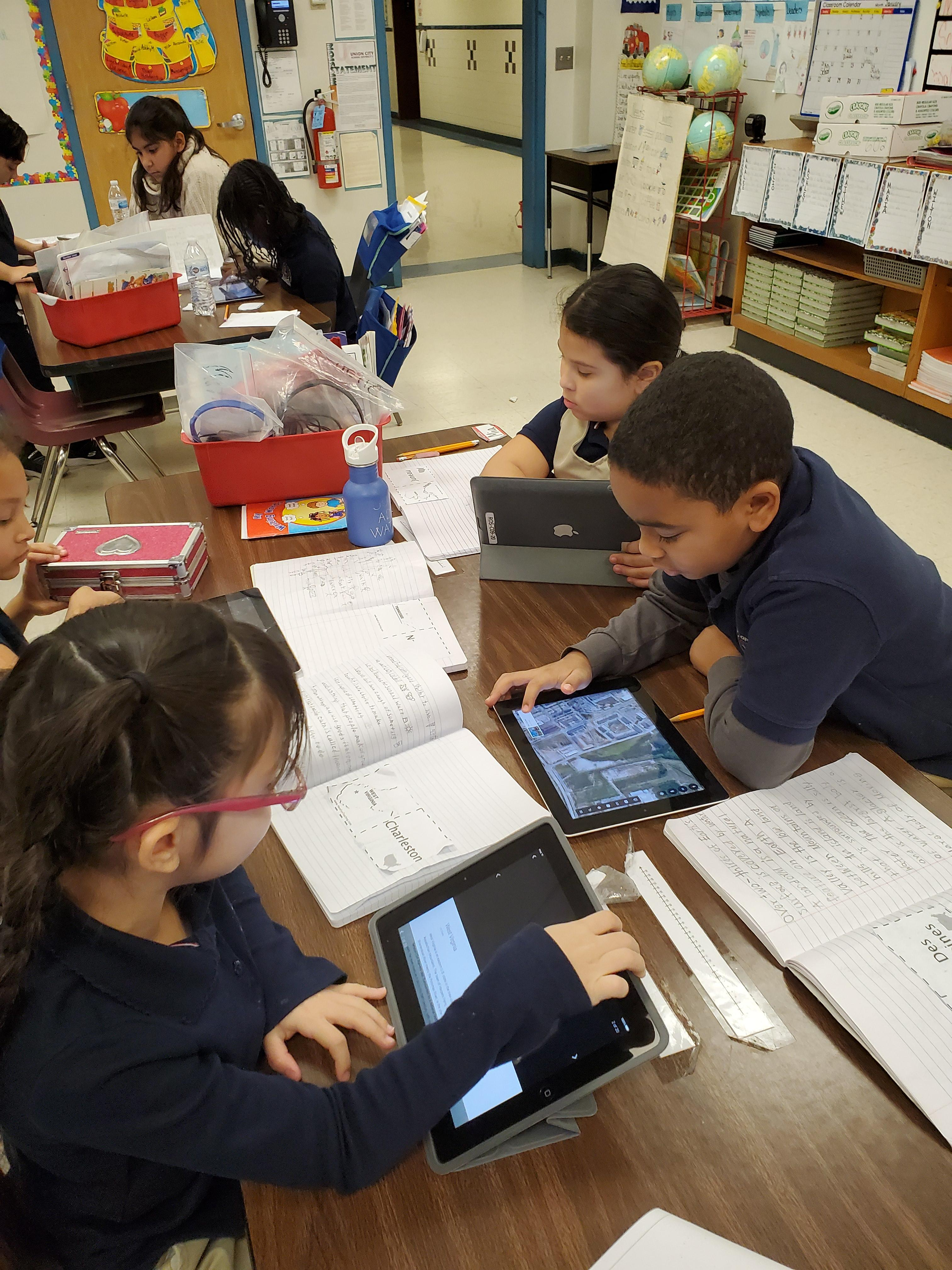 several children seated at desks with designated cities and using ipads to look the up